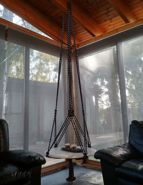 einladende sitzecke im wohnzimmer einrichten mit rundem hängetisch aus holz als beistelltisch zwischen zwei ledersesseln in schwarz