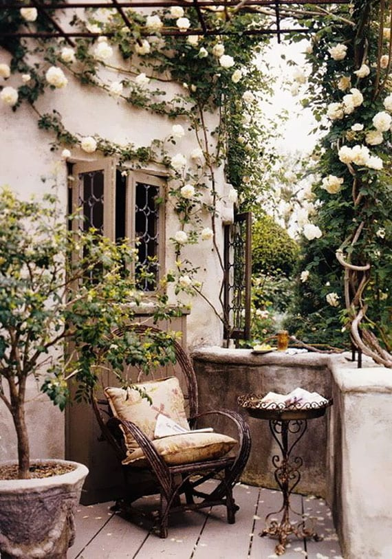 romantische gartengestaltung mit weißen kletterrosen und sitzecke im garten mit altem rattansessel und rundem metall-beistelltisch einrichten