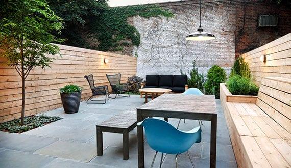 den-kleinen-Hofgarten-funktional-und-attraktiv-gestalten-mit-Zaun-als-Sichtschutz-und-Sitzbank-mit-Hochbeeten-in-einem