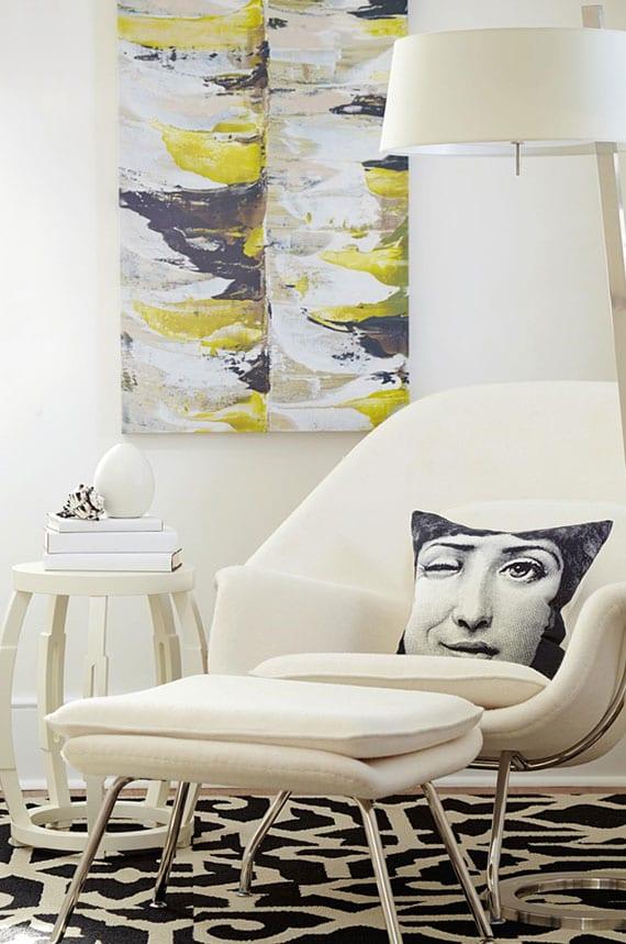 wohnzimmer oder schlafzimmer wohnlich einrichten mit einem bequemen Lesesessel mit Hocker in weiß, moderner Stehelampe, kleinem Beistelttisch rund und abstraktem Gemälde als frische wanddeko