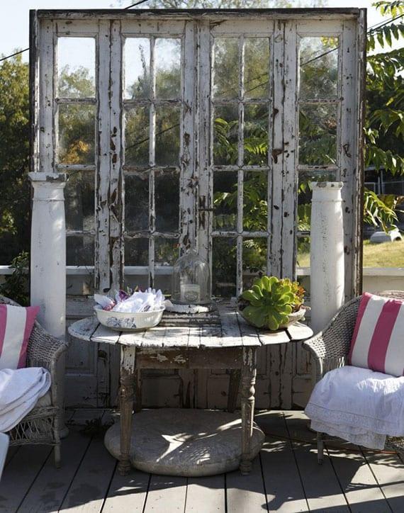idee für gemütliche sitzecke im garten mit rattanstühlen, rustikalem holztisch rund, alter zweiflügeltür mit sprossenfenstern und dekorativen säulen als Kulisse der sitzecke