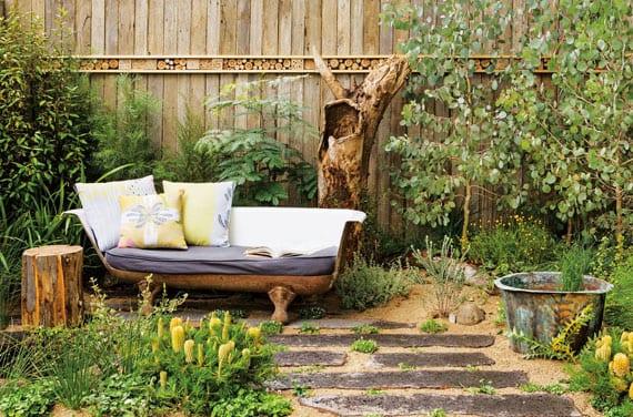 originelle gartengestaltung und gartendekoration mit Vintage-Badewanne auf Füßen als DIY Gartensofa mit Beistelltisch aus Baumstam, holzmauer, gartenweg aus steinplatten