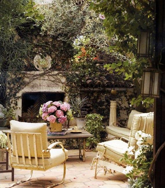 attraktive gartengestaltung mit kletterpflanzen, außenkamin,pflasterboden, weißen vintage-gartenmöbeln aus metall mit polsterkissen, kaffeetisch metall mit steintischplatte und rosafarbiger hortensie im topf als tischdeko