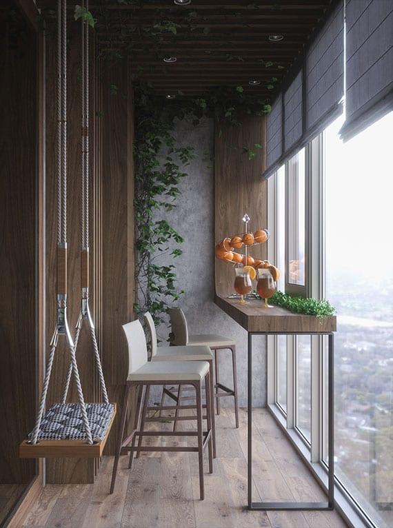 der kleine balkon als modern eingerichtete sitzecke mit holzschaukel, bartheke mit barhockern, holzwandverkleidung, kletterpflanze und stoffrollos