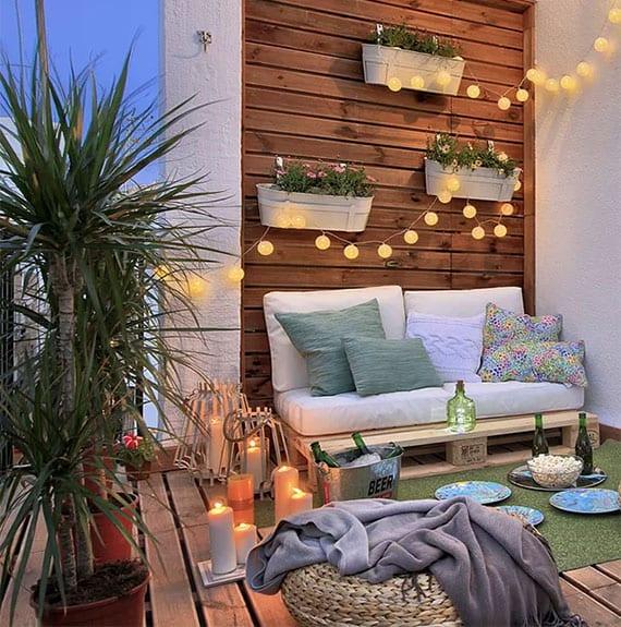 kleiner balkon vertikal begrünen mit pflanzen in wandhängenden blumentöpfen weiß, wandverkleidung holz, palettensofa, sitzkissen rattan, kerzendeko