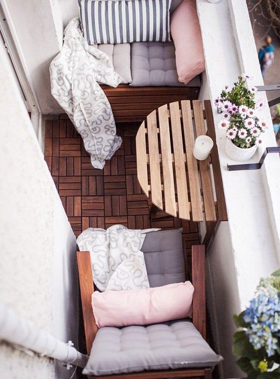 kleiner balkon gemütlich einrichten mit halbrundem klapptisch holz und holzkiste als bewahrungsmöglichkeit und sitzbank mit sitzkissen in pastellfarben