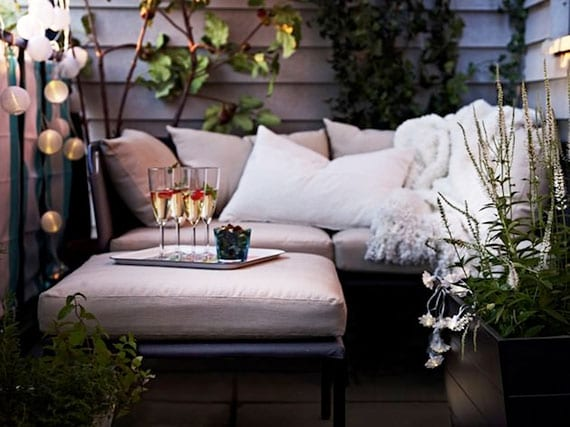den kleinen balkon romantisch und gemütlich einrichten mit kleinem gartensofa und hockertisch aus metall, lichterkette, kletterpflanzen und saisonblumen weiß und kuschelliger decke in kombination mit weißen dekokissen