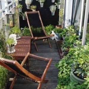 ideen-für-balkongestaltung-mit-vielen-pflanzen-und-modernen-ruhesesseln-aus-holz