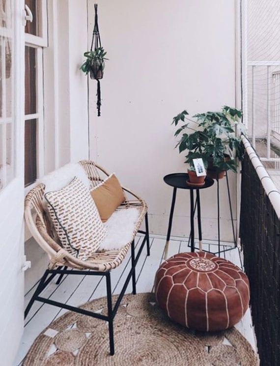 kleiner balkon in weiß mit holbodenbelag, rattansitzbank,beistelltisch und pflanzenständer aus metall, polsterhocker aus leder, sichtschutz schwarz und rundem teppich