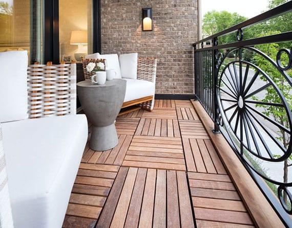 kleiner balkon modern und stilvoll gestalten mit holzbodenbelag, eisengeländer schwarz, moderne gartenmöbeln aus holz mit weißen postersitzen und rundem betontisch