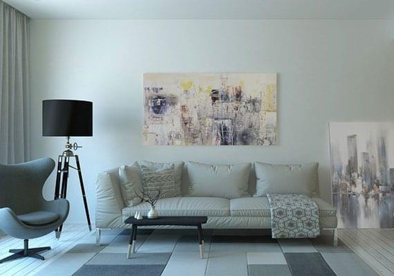 wohnzimmergestaltung mit ledersofa weiß, designer sessel grau, moderner stehlampe in schwarz, kleinem couchtisch holz, gemälden als wanddeko