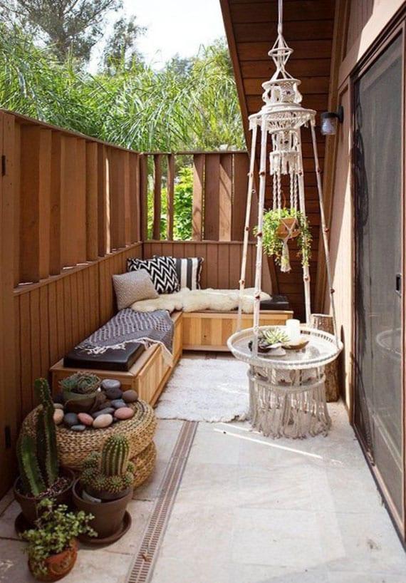 coole gestaltungsidee für kleine balkone mit ecksitzbank aus holz, teppich auf betonboden, rattansitzkissen und diy kafeetisch rund aus makramee