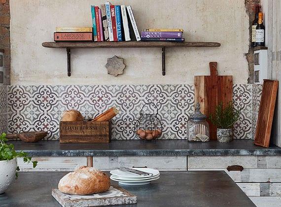 küche in meditarranen stil mit küchenrückwand aus gemusterten wandfliesen, rustikalen holzküchenschränken und küchenarbeitsplatte in grau, diy holewandregal für kochbücher