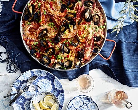 mediterranes Flair in die Küche holen mit blauen tischdecken, authentischen tellern und typische paella pfanne