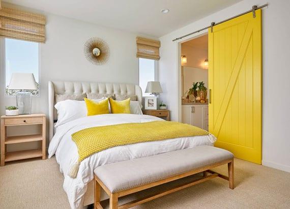 schlafzimmer mit bad in mediterranen stil einrichten mit doppelbett mit polsterkopfteil und sitzbank, holznachttischen mit tischlampen glas,holzschiebetür gelb, fenstersonnenschutz mit bambusrollos