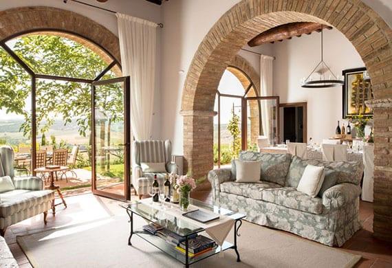 attraktives wohnzimmer interior mit ziegelbögen,rundbogen-verglasung und weißen gardinen,klassischem sofa mit blumenmuster, polsterssels und glascouchtisch auf teppich beige, terracotta fliesen braun