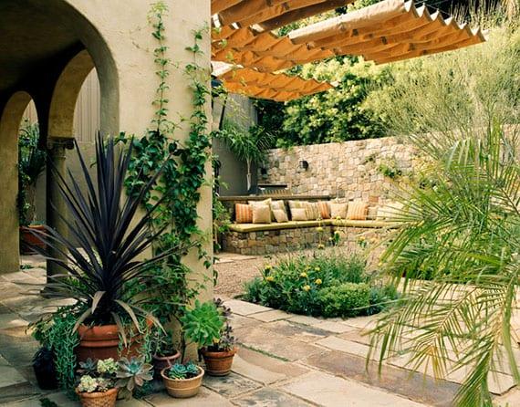 attraktive mediterranne gartengestaltung mit gartensitzecke aus gemauertem eckbank mit kissen, holzpergola mit sonnensegel,kreutergarten und pflanzen in blumentopfen aus ton