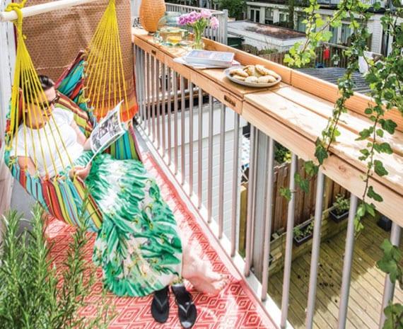 kleiner balkon mit bunten interieur, schaukel, teppich und bartheke aus holz entlang dem balkongeländer