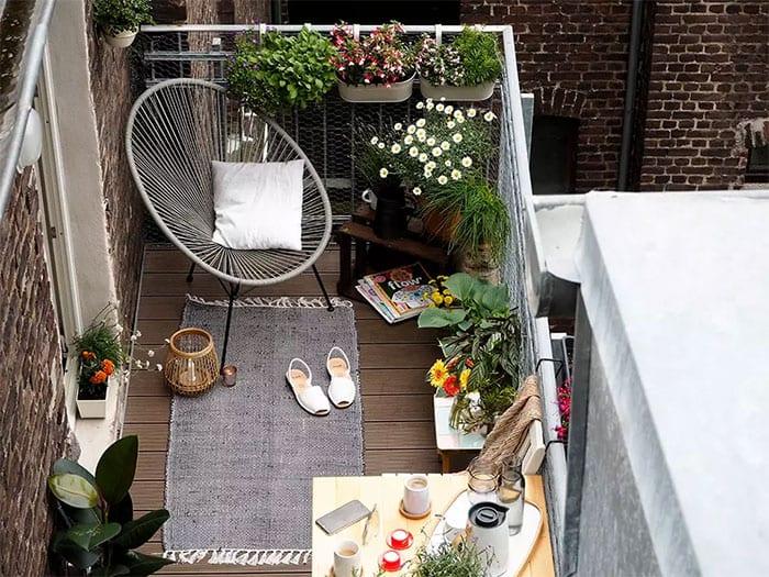gestaltungsidee für rustikalen balkon mit holzdiele, klapptisch gelb, designer ruhesessel und teppich in grau,saisonblumen in metallkästen für geländer