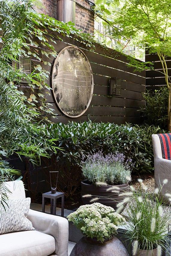 garten modern und attraktiv einrichten mit polster-möbeln auf kiesboden, blumen in scwarzen blumenkübeln und rundem wandspiegel als akzent zum schwarz gestrichener holzwand mit kletterpflanzen