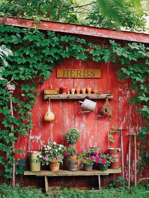 coole deko tipps und ideen für einen vintage gartenecke mit kräutern im blumentöpfen, holzzaun mit kletterpflanzen als rustikaler akzentwand in rot, diy vogelhaus