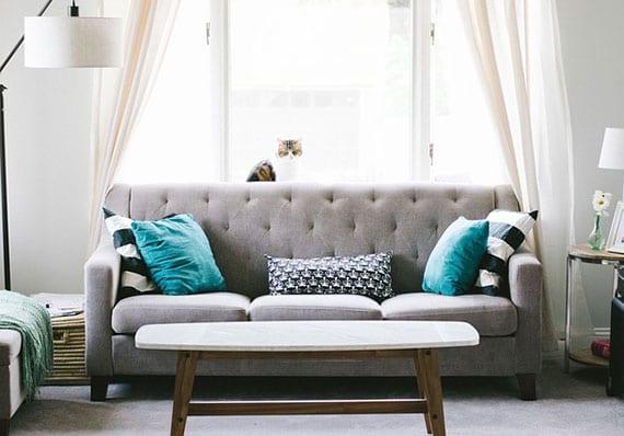 kleines wohnzimmer wohnlich einrichten mit polstersofa grau, dekokissen in türkis und kaffeetisch holz vor fenster mit gardinen in creme