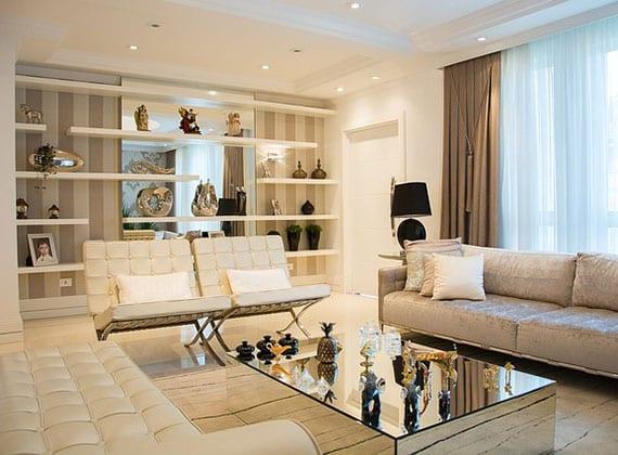 schicke wohnzimmereinrichtung mit weißen liege und sesseln aus leder, modernem sofa und couchtisch aus spiegelglas, akzentwand mit streifentapette, wandspiegel und weißen regalen, fensterdeko mit weißen gardinen und vorhängen in braun