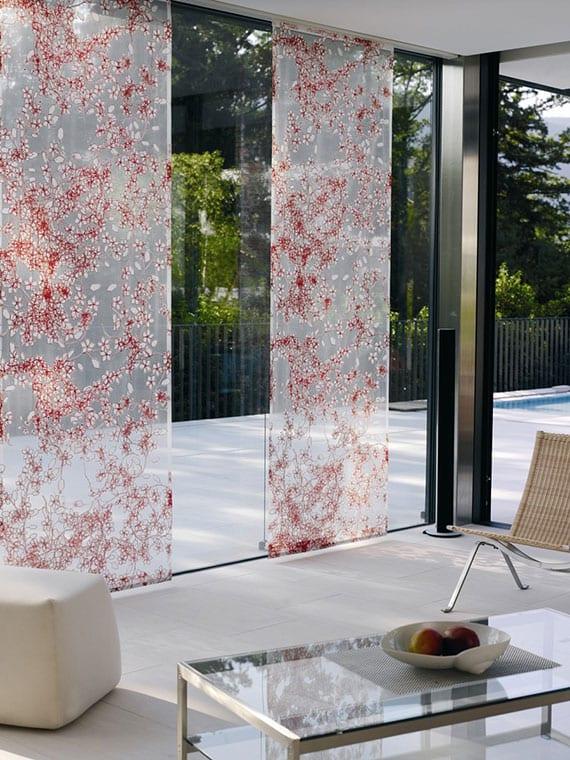 elegante schiebevorhänge mit rotem blumenmotiv als sonnenschutz und gestaltungselement im modernen interieur mit bodentiefen fenstern