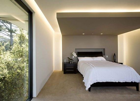 schlafzimmer modern und gemütlich gestalten durch indirekte wand- und deckenbeleuchtung, panoramafenster im schwarzen rahmen, holzbett mit kopfteil schwarz