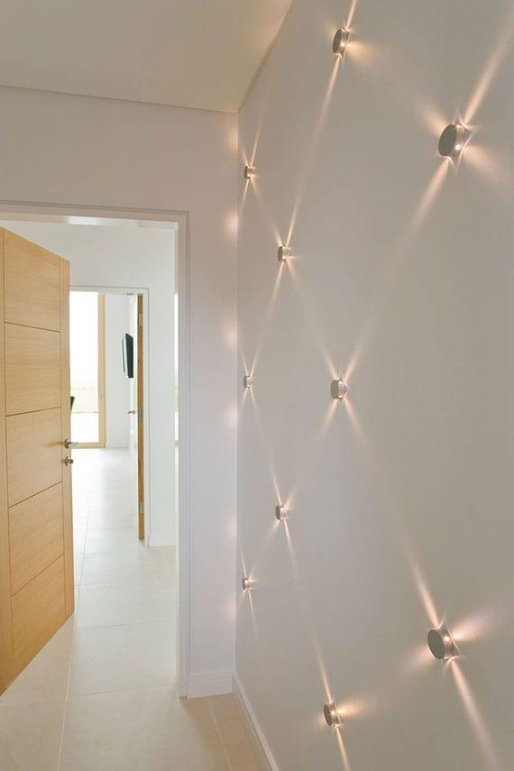 kreative Raumgestaltung mit mehreren LED Wandleuchten als attraktives Lichtakzent im Flur mit weißen wänden und holzzimmertüren
