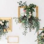 attraktive wanddekoration mit frischen blumen und grünes in goldenen bilderrahmen