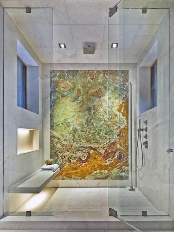 attraktives badezimmer interior design mit akzentwand aus buntem naturstein, indirektbeleuchtete wandnische, betonbank, zwei fenstern im duchbereich