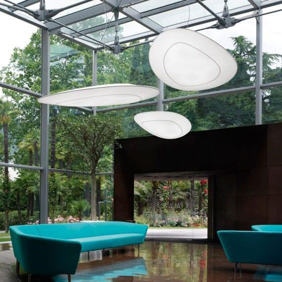 modernes interieur design mit glasfassade, hochem glasdach und designer pendellampen über sitzecke von zwei soffas mit minimalistischem design in blau