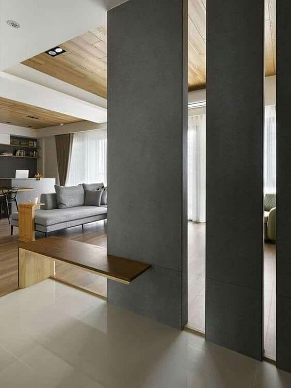 stilvolle raumgestaltungsidee mit wandpaneelen und einfacher holzsitzbank als luftiger raumteiler lösung zwischen modernem wohnzimmer holzdeckenverkleidung und eingangsbereich mit wißen bodenfliesen