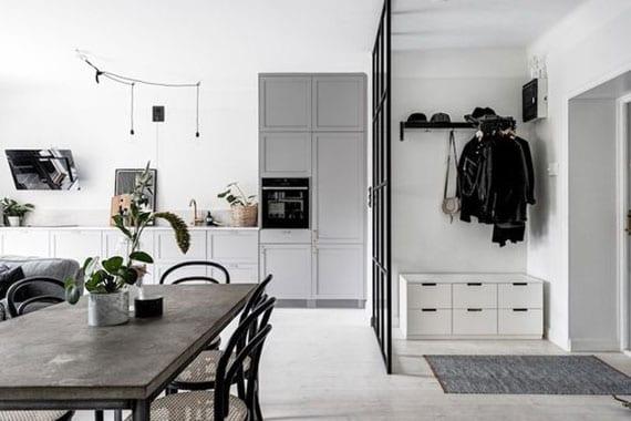 einzimmerwohnung im skandinavischem stil mit trennwand aus glas zwischen wohnküche grau mit betonesstisch und eingangsbereich mit schuhschrank und sitzbank in weiß