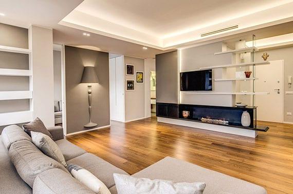 offenes wohnzimmer interior in weiß und grau mit holzbodenbelag, kreativer wandleuchte und moderner tv-Wand mit kamin als raumteiler