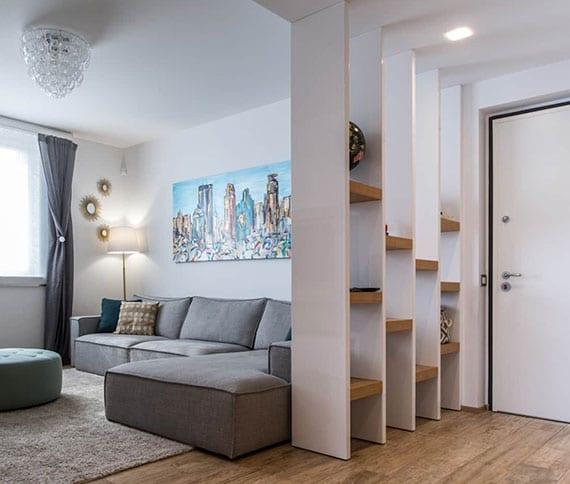 coole raumgestaltung kleiner wohnung mit offenem regalsystem aus holz als moderner raumteiler zwischen kleinem wohnzimmer mit ecksofa grau und eingangsbereich