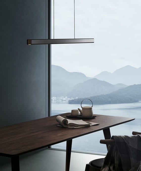 puristische raumgestaltung mit eleganter pendellampe in schlichter rechteckform entlag moderner holzesstisch im esszimmer mit panoramafenster und wandfarbe schwarz