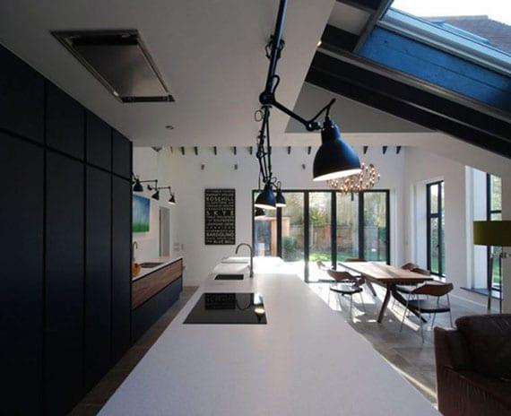 moderne küche mit dachfenstern über kochinsel weiß, schwarzem küchenschrank, essbereich mit holzesstisch und designer-stühlen, bodentiefer verglasung und drehebaren pendellampen im industriellen stil