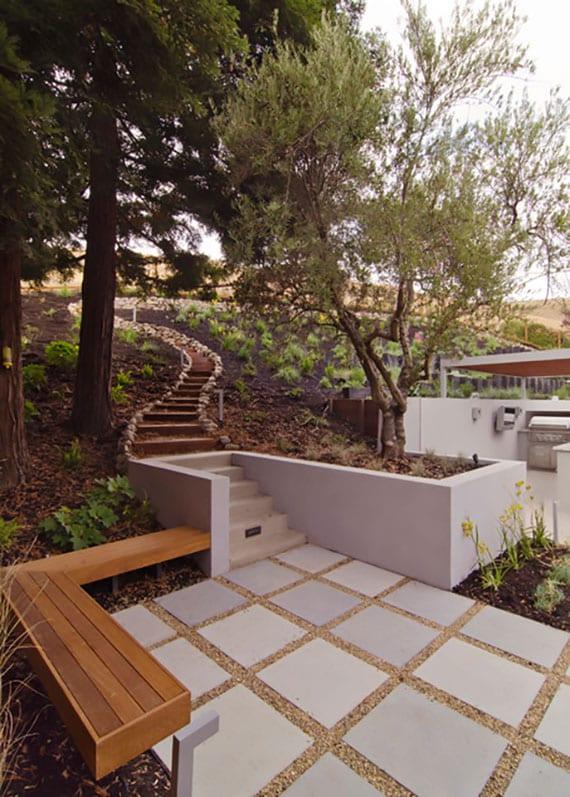 attraktive hanggarten design mit gartentreppe aus holzbalken, stützmauern aus beton und kleiner terrasse mit rechteckigen und eckgartenbank holztrottsteinen