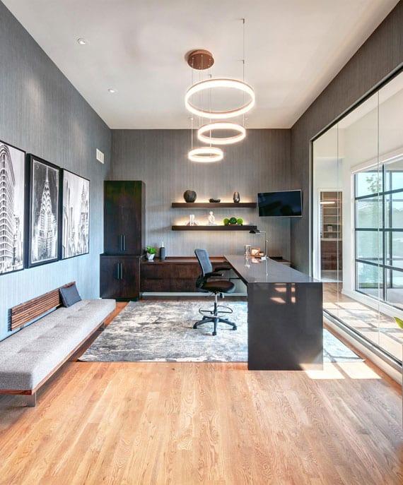 stilvolle raumgestaltungsidee für modernes homeoffice mit schwarzem bürotisch in hochglanz, polstersitzbank entlang wand, holzregale mit indirekter beleuchtung, glastrennwand zum korridor und eleganten ring-pendelleuchten