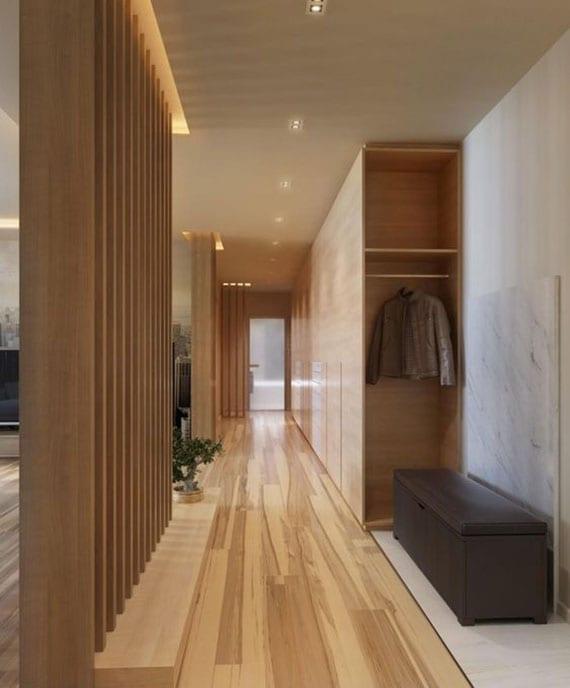 flur und eingangsbereich in moderner open-space-wohnung durch indirekte deckenbeleuchtung und trennwand aus vertikalen holzlatten vom offenem wohnzimmer trennen