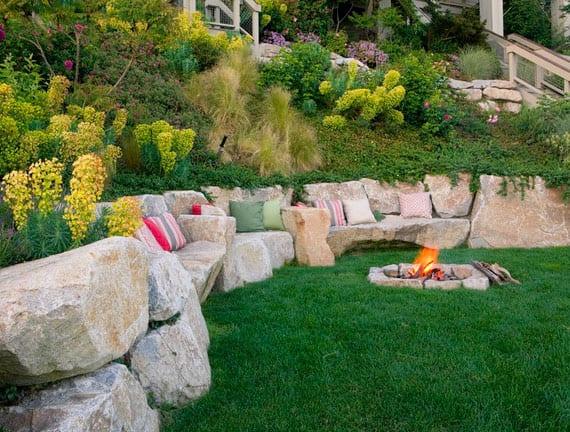 traumgarten am hang mit stützmauer aus findlingen als sitzecke mit feuerplatz