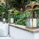 der kleine garten stilvoll gestalten mit gemauerter sitzbank mit polstern, prachvollen gartenblumen und großen metall-laternen mit weißen kerzen