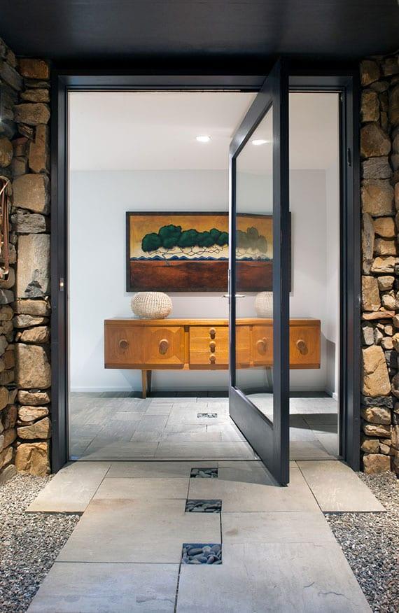einfamilienhaus mit moderner arhitektur und attraktiver gestaltung des eingangsbereiches durch natursteinmauer, schwenktur glas und bodenfliesen in kiesbett
