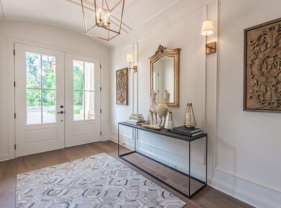eingangsbereich gestalten modern und elegant im klassischen stil mit weißer doppelflügeltür mit glas, dunklem holzboden, modernem sideboard schwarz, wanddeko mit spiegel in goldrahmen , holzkunstwerken und wandleuchten