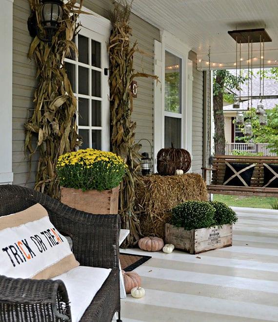 coole eingangsdeko zu halloween mit kleinen kürbissen, maisstängeln,chrysanthemen in holzkisten und laterne auf heuballen