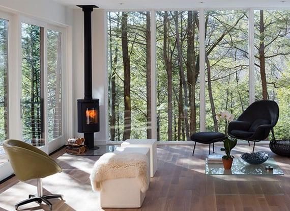 wohnzimmer skandinavisch einrichten mit kleinem kamin rund, gemütlicher sitzecke mit sesseln um glaskaffeetisch und traumhaften blick auf wald durch bodentiefe verglasung