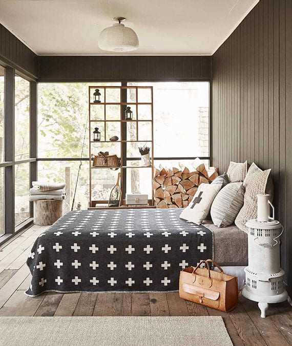stilvolle schlafzimmer gestaltung im rustikalen stil mit natürlichem holzboden, dunkelgrau geschrichener holzwandverkleidung, bodentiefen fenstern und natürlicher zimmerdeko mit feuerholz und vintage-kaminofen in weiß