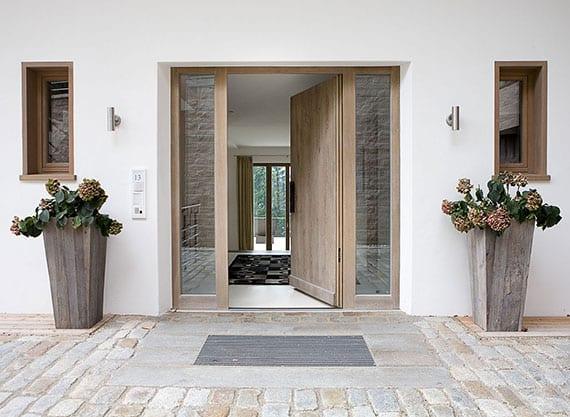 eingangshaustür in holzoptik mit fenstern in blendrahmen als gestaltungstrend in moderner arhitektur der einfamilienhäuser